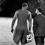 Football player and man in suit walking together